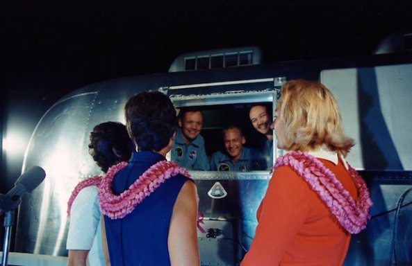 Apollo 11 astronauts, still in quarantine van, are greeted by wives upon arrival at Ellington Air Force Base.