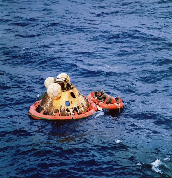Apollo 11 crewmen await pickup by helicopter following splashdown.
