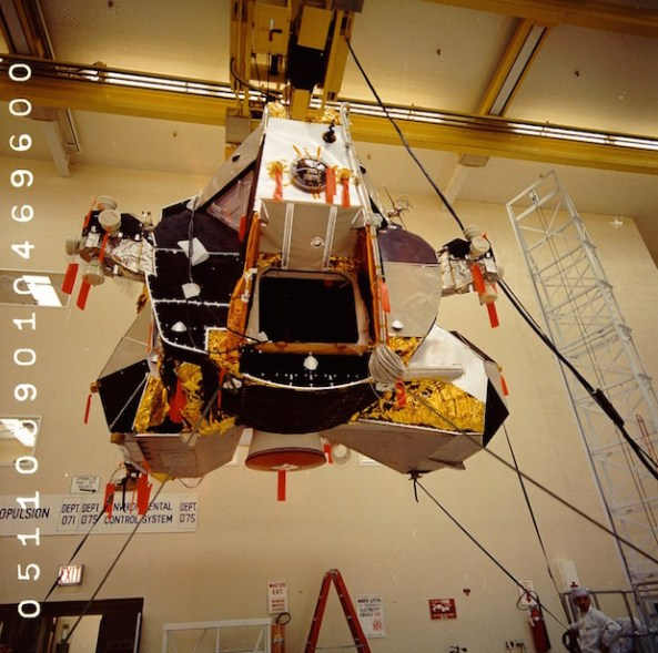 Lunar Module 5 is held in place via an overhead hoist before inspection.